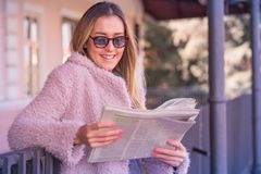 Donna che sta alla stazione ferroviaria e che legge i giornali Fotografia Stock Libera da Diritti