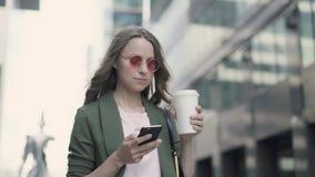 Donna che sta in caffè praticante il surfing e bevente di web della via della città video d archivio