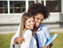 Donna che sta con il braccio intorno all'amico sulla città universitaria Fotografie Stock Libere da Diritti