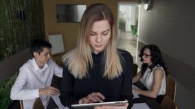 Donna che sta con il computer portatile ed i suoi colleghi su fondo archivi video