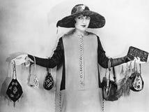 Donna che sta con le sue armi a parte che indossano le borse (tutte le persone rappresentate non sono vivente più lungo e nessuna fotografia stock