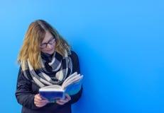 Donna che sta contro il libro di lettura della parete Immagine Stock Libera da Diritti