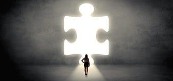 Donna che sta davanti ad un grande pezzo di puzzle fotografia stock