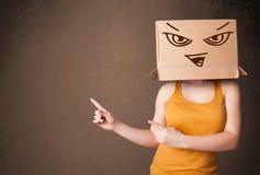 Donna che sta e che gesturing con una scatola di cartone sulla sua testa con il fronte diabolico immagini stock libere da diritti