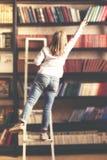 Donna che sta e che raggiunge per un libro Fotografia Stock
