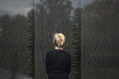 Donna che sta esaminante i nomi sul memoriale Washington del Vietnam fotografie stock