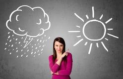 Donna che sta fra un sole e un disegno della pioggia Fotografia Stock Libera da Diritti