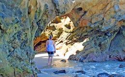 Donna che sta l'arco interno in Laguna Beach, California della linea costiera fotografie stock libere da diritti