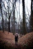Donna che sta nel fondo freddo scuro della foresta Fotografia Stock
