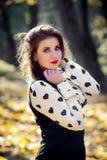 Donna che sta nel parco mentre esaminando macchina fotografica Fotografia Stock