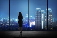 Donna che sta nel suo ufficio che esamina la città la notte Immagini Stock