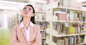 Donna che sta nella biblioteca mentre pensando stock footage