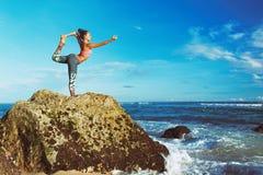 Donna che sta nella posa di yoga sulla roccia della spiaggia del mare Immagini Stock