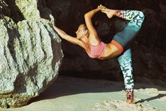 Donna che sta nella posa di yoga sulla roccia della spiaggia del mare Immagine Stock