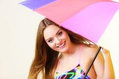 Donna che sta sotto l'ombrello variopinto dell'arcobaleno fotografia stock libera da diritti