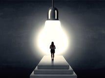 Donna che sta su un punto davanti ad una lampadina enorme Fotografia Stock