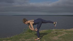Donna che sta su una gamba, addestramento dell'equilibrio, yoga archivi video