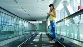 Donna che sta sul passaggio pedonale automatico, scale nell'incrocio del sottopassaggio, facendo uso del suo telefono, un mezzo d archivi video