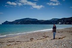 Donna che sta sulla spiaggia Immagini Stock
