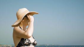 Donna che sta sulla spiaggia con il suo cappello operato archivi video