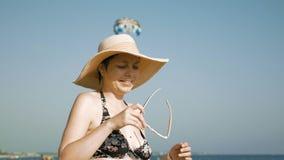 Donna che sta sulla spiaggia con il suo cappello operato stock footage