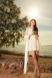 Donna che sta sulla spiaggia che tiene tulipano rosa Immagini Stock
