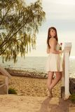 Donna che sta sulla spiaggia che tiene tulipano rosa Immagine Stock Libera da Diritti