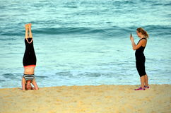 Donna che sta sulla sua testa e che fa yoga sulla spiaggia fotografia stock libera da diritti