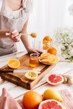 Donna che sta tavola vicina con gli agrumi e che tiene miele Fotografia Stock Libera da Diritti