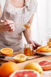 Donna che sta tavola vicina con gli agrumi e che tiene miele Immagine Stock Libera da Diritti