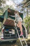 Donna che sta in tenda di apertura della scala sopra l'automobile immagini stock libere da diritti