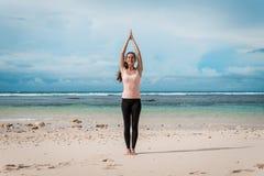 Donna che sta una posa di yoga del namaste sulla spiaggia accanto all'oceano o al mare in tempo nuvoloso Zen, meditazione, pace S immagini stock libere da diritti