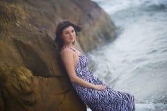 Donna che sta vicino ad una roccia sui precedenti dell'oceano di estate fotografie stock libere da diritti