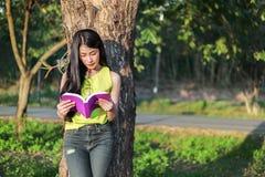 Donna che stading all'albero e che legge un libro nel parco Immagine Stock