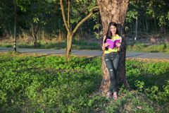 Donna che stading all'albero e che legge un libro nel parco Immagini Stock