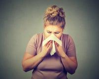 Donna che starnutisce soffiando il suo naso semiliquido Immagini Stock