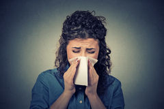 Donna che starnutisce in un tessuto che soffia il suo naso semiliquido Immagine Stock