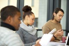 Donna che studia duro per gli esami in biblioteca Immagini Stock Libere da Diritti