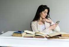 Donna che studia per gli esami con il telefono nella mano Fotografia Stock Libera da Diritti