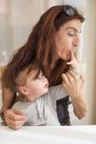 Donna che succhia il cioccolato del dito del bambino Fotografia Stock Libera da Diritti
