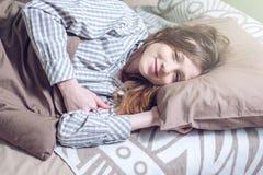 Donna che sveglia di mattina, trovarsi sonnolenta a letto Immagine Stock Libera da Diritti