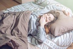 Donna che sveglia di mattina, trovarsi sonnolenta a letto Fotografia Stock