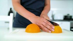 Donna che taglia arancia in una cucina moderna video d archivio