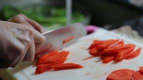 Donna che taglia carota a pezzi video d archivio