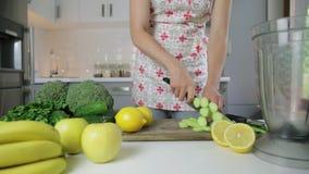 Donna che taglia le verdure a pezzi verdi per il frullato della disintossicazione a casa Cibo sano, alimento vegetariano, stante  video d archivio