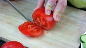 Donna che taglia un pomodoro con un coltello video d archivio
