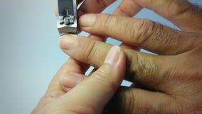Donna che taglia unghia dal dito del ` s dell'uomo Fotografie Stock