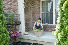Donna che tende recentemente alle piante in vaso sul suo patio immagini stock