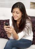 Donna che texting utilizzando un telefono mobile nella casa Immagini Stock Libere da Diritti