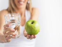 Donna che tiene bicchiere d'acqua e mela verde. immagini stock